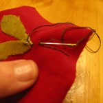 make a line using embroidery floss. Start at the leaf and then stitch to the top of garland piece