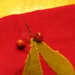 sew two wooden beads at the top of leaves