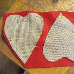 cut out hearts from felt fabric that is slightly larger than the burlap heart